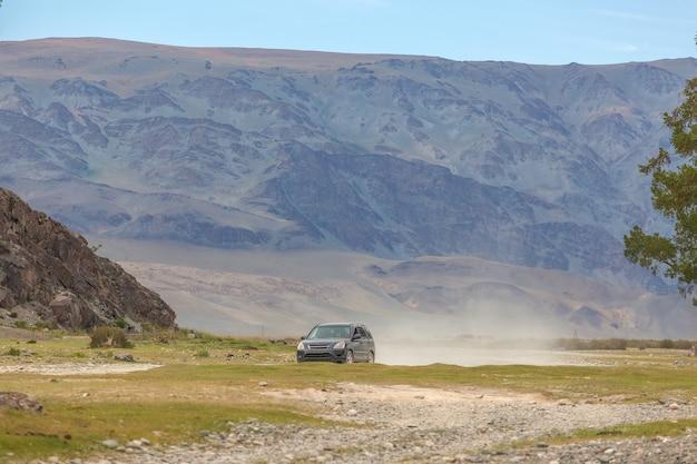 차는 몽골의 대초원을 탄다. 많은 먼지, 산을 배경으로합니다.