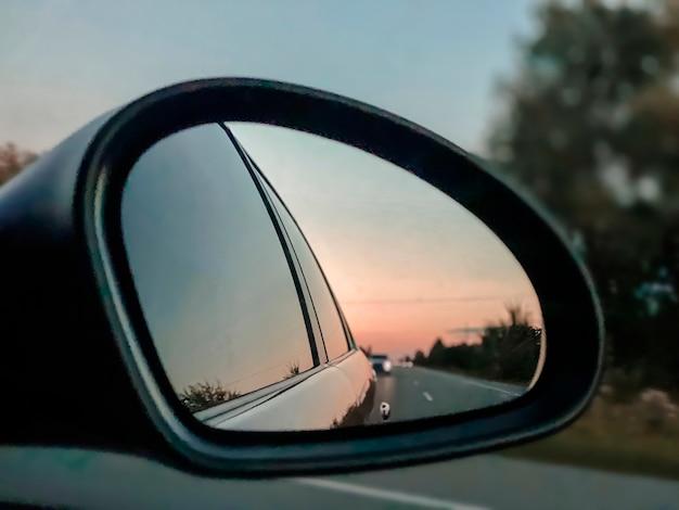 Зеркало заднего вида автомобиля показывает вид на дорогу и машины сзади на шоссе. концепция авто путешествия.