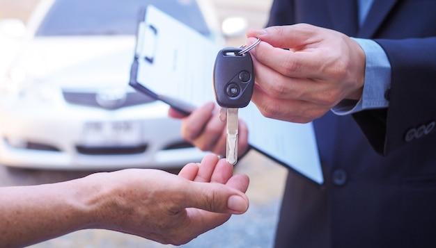 자동차 판매원과 새로운 소유자의 열쇠.