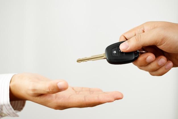 Продавец автомобилей вручает ключи от машины покупателям в автосалоне.