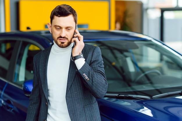 車は男性の性格を示しています。完全なスーツと新しい青い車の近くに立って手に電話で自信を持って成功するエレガントなビジネスの男性は目をそらします