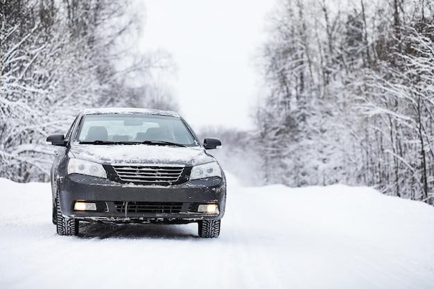 Машина стоит на заснеженной дороге в зимний пасмурный день
