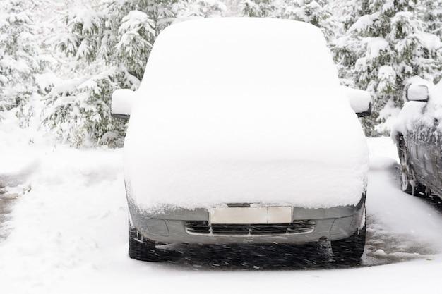 雪の層の下の車