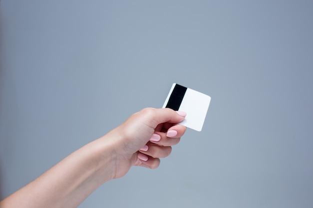 女性の手のカードは灰色の背景に
