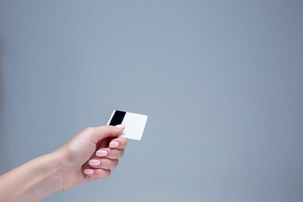 女性の手のカードは灰色の壁にあります