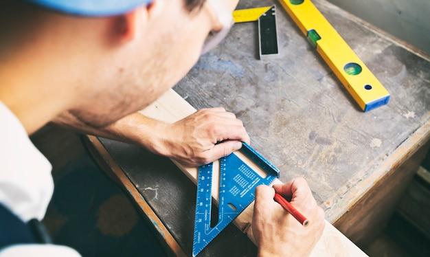 Плотник рисует линию карандашом на деревянной доске.