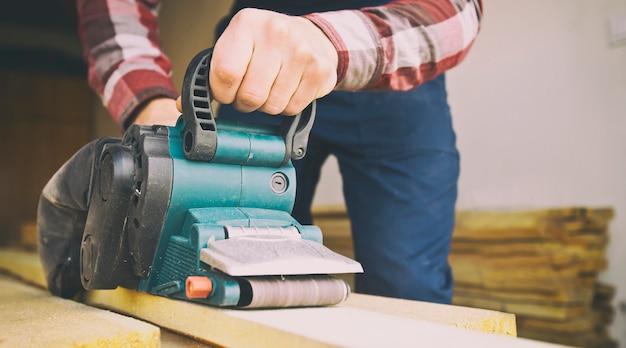 Плотник обрабатывает древесину ленточной шлифовальной машиной