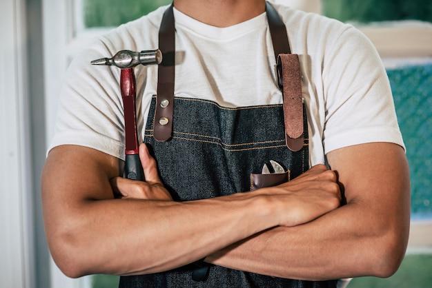 Плотник стоит и держит молоток.
