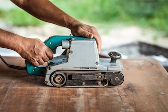 The carpenter uses power sander as a powerful tool in wood finishing.