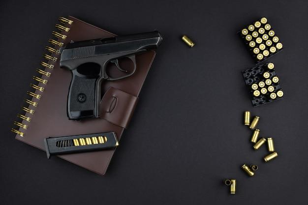 카트리지는 권총과 장전 된 탄창이 갈색 가죽으로 묶인 공책에 놓여 있습니다.