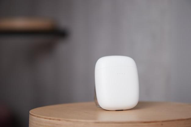 무선 헤드폰 케이스는 테이블 위에 있으며 헤드폰의 닫힌 덮개는 배경이 흐릿합니다.