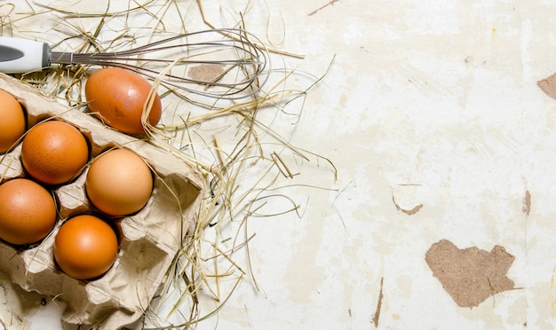Кассета с яйцами, сеном и венчиком. на деревенском столе. свободное место для текста. вид сверху