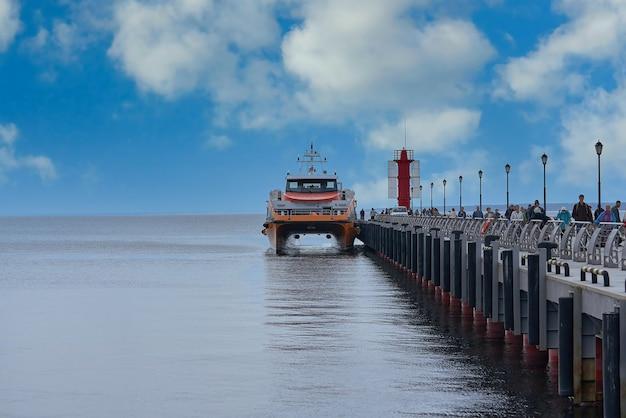 쌍동선 여객선은 바다 부두에 정박해 있습니다. 편안한 해상 여객 운송