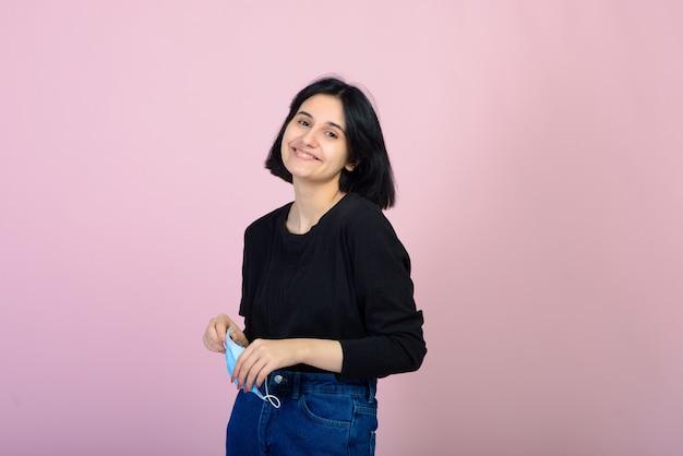 Кавказская девушка в синей защитной маске. портрет выстрелил на розовом фоне. концепция защиты от вирусов