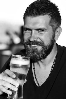 Концепция фестиваля октоберфест празднования. наслаждайтесь в пабе. красивый бородатый мужчина пьет пиво