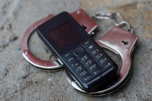 携帯電話は手錠で横になっています。高品質の写真