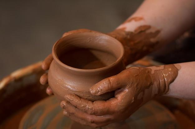陶芸家は既製の土鍋を手に持っています