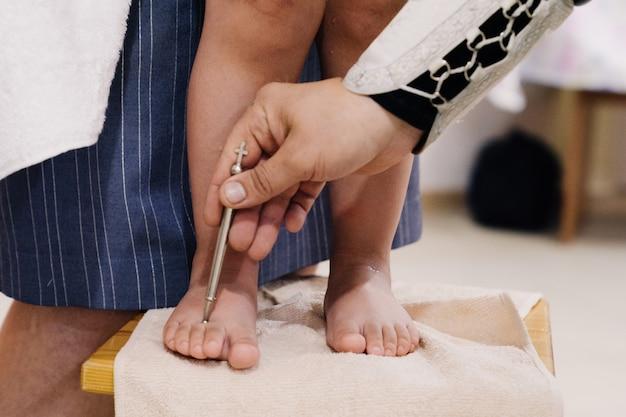 キリスト教会での洗礼式。子供の足の僧侶のタッチ
