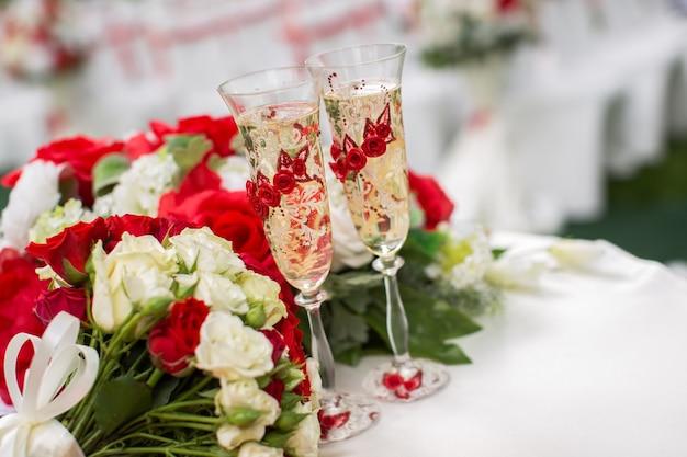 샴페인 잔. 야외 결혼식. 붉은 꽃과 꽃다발입니다.