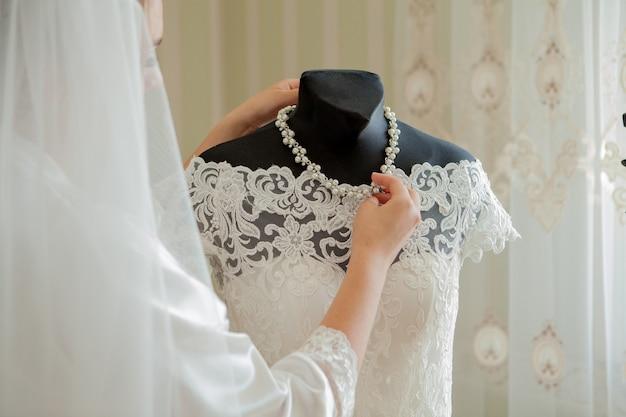 신부 들러리가있는 매력적인 신부가 웨딩 드레스 근처에 서 있습니다.