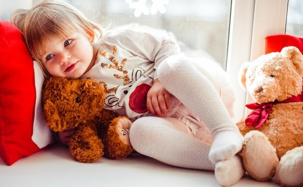 Очаровательная дочь лежит на подоконнике