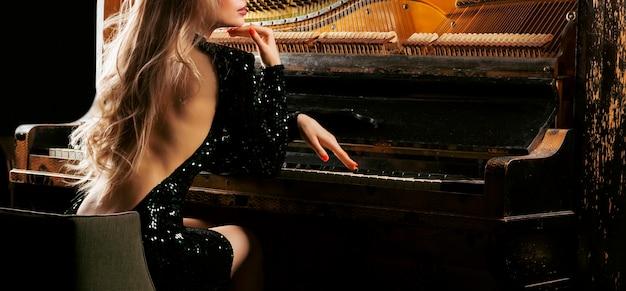 이브닝 드레스를 입은 매력적인 소녀가 오래된 독일 피아노를 연주합니다. 뒷모습. 개념적 매체