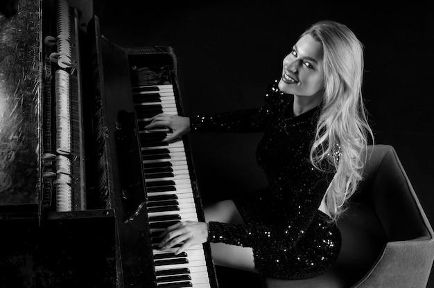 이브닝 드레스를 입은 매력적인 소녀가 오래된 독일 피아노를 연주합니다. 위에서 볼 수 있습니다. 개념적 매체