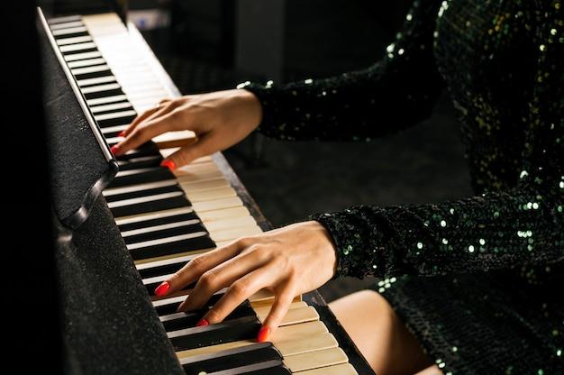 イブニングドレスを着た魅力的な女の子が古いドイツのピアノを弾きます