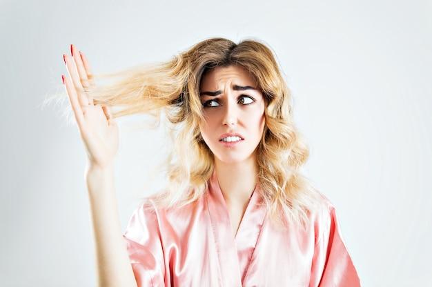 Очаровательная девушка с ужасом смотрит на секущиеся кончики волос.