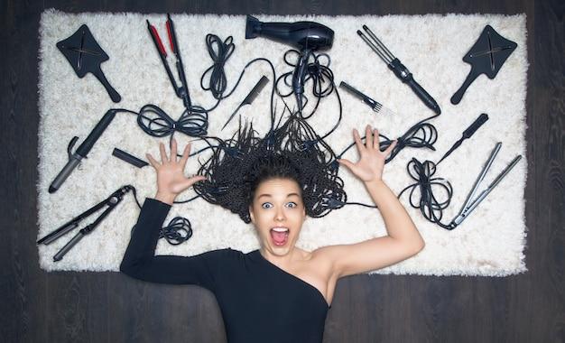 Очаровательная девушка развела руками в стороны и кричит. на фоне инструментов для создания стрижки