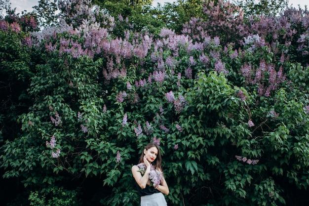 魅力的な女の子は花の茂みの近くに立つ