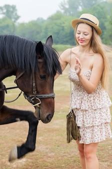 말과 함께 밀짚 모자와 여름 드레스에 밝은 금발