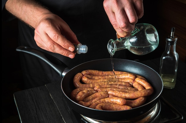 요리사는 생고기 소시지와 함께 팬에 기름을 추가합니다. 야채와 함께 테이블에 레스토랑이나 카페의 부엌에서 소시지 요리 준비