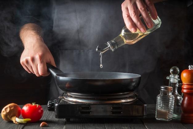 シェフが調理中に鍋にオリーブオイルを追加します