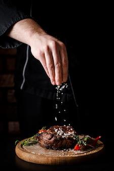 Шеф-повар готовит вкусный стейк из свинины
