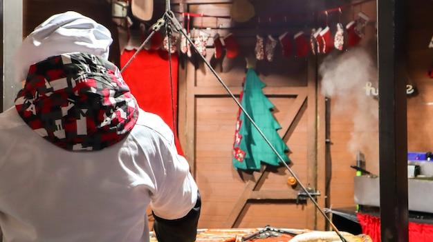 シェフは焼きケバブ、屋台の食べ物、料理の饗宴を調理します。新鮮なソーセージとグリルを屋外で。男がドイツ料理の屋台の食べ物を準備しています。ヨーロッパのクリスマスマーケット。フェスティバルシティフェア。