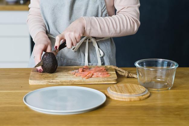 요리사는 연어와 계란 샌드위치를 만들기 위해 avacado를 자릅니다.