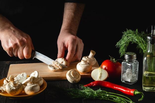 Шеф-повар режет грибы ножом, чтобы приготовить вкусные блюда.