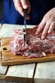 シェフがまな板で生肉を切る