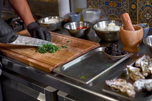 Шеф-повар нарезает зелень, готовит ингредиенты для блюда на столе на кухне.