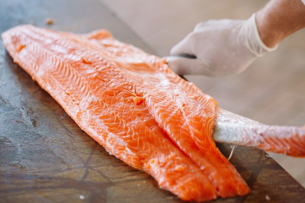 Шеф-повар режет лосося на столе.