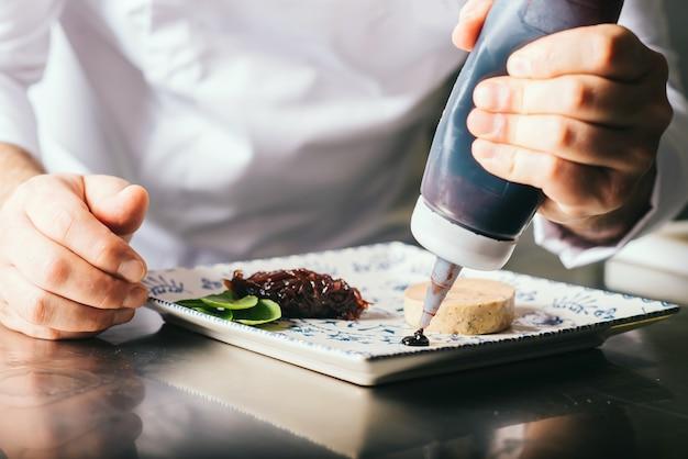 Шеф-повар украшает тарелку фуа-гра соусом.