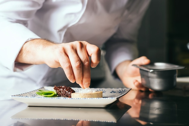 Шеф-повар украшает тарелку фуа-гра