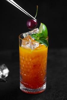 셰프는 핀셋으로 체리 베리로 오렌지색 냉각 주스를 장식합니다. 낮은 키