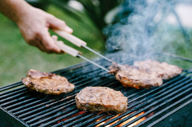 요리사는 집게로 연기와 불로 금속 그릴에서 고기를 뒤집습니다