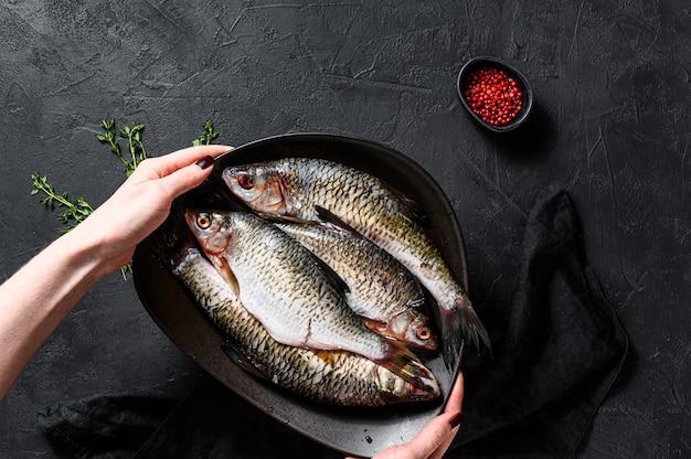 Шеф-повар держит тарелку карась. речная органическая рыба. черный фон. вид сверху. пространство для текста