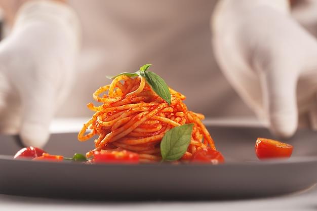 Шеф-повар держит в руках в перчатках тарелку с пастой в томатном соусе.