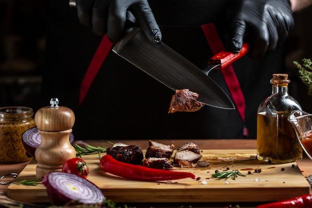 검은 장갑을 입은 요리사가 칼로 쇠고기 필레를 자릅니다.