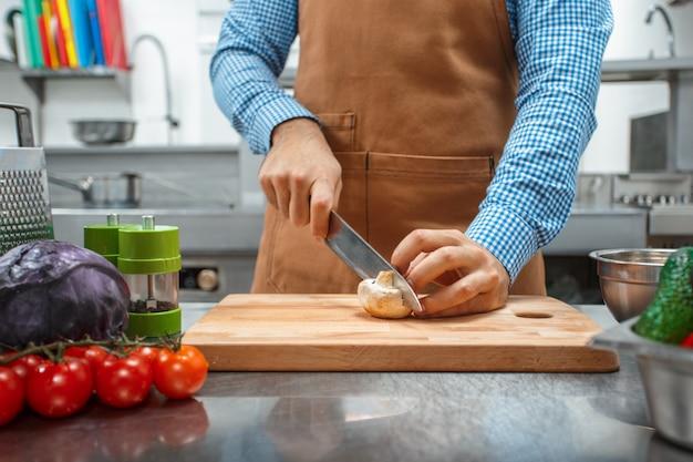 Шеф-повар в коричневом фартуке готовит на кухне ресторана