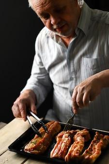Шеф-повар выкладывает маринованные свиные ребрышки на противень. готовим ребрышки.